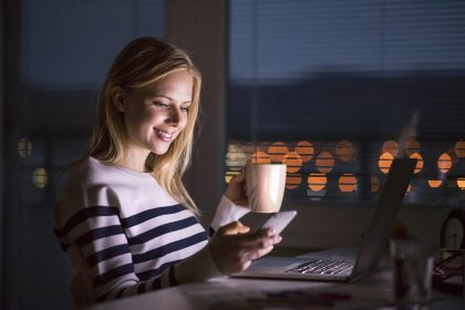 Habits - woman at desk, holding smartphone, working on laptop at night.